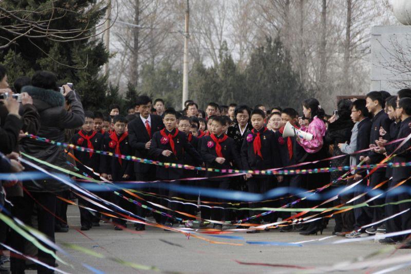 Học sinh diễu hành qua một con đường giăng kín bằng giấy màu trước khi buổi lễ Khai giảng bắt đầu